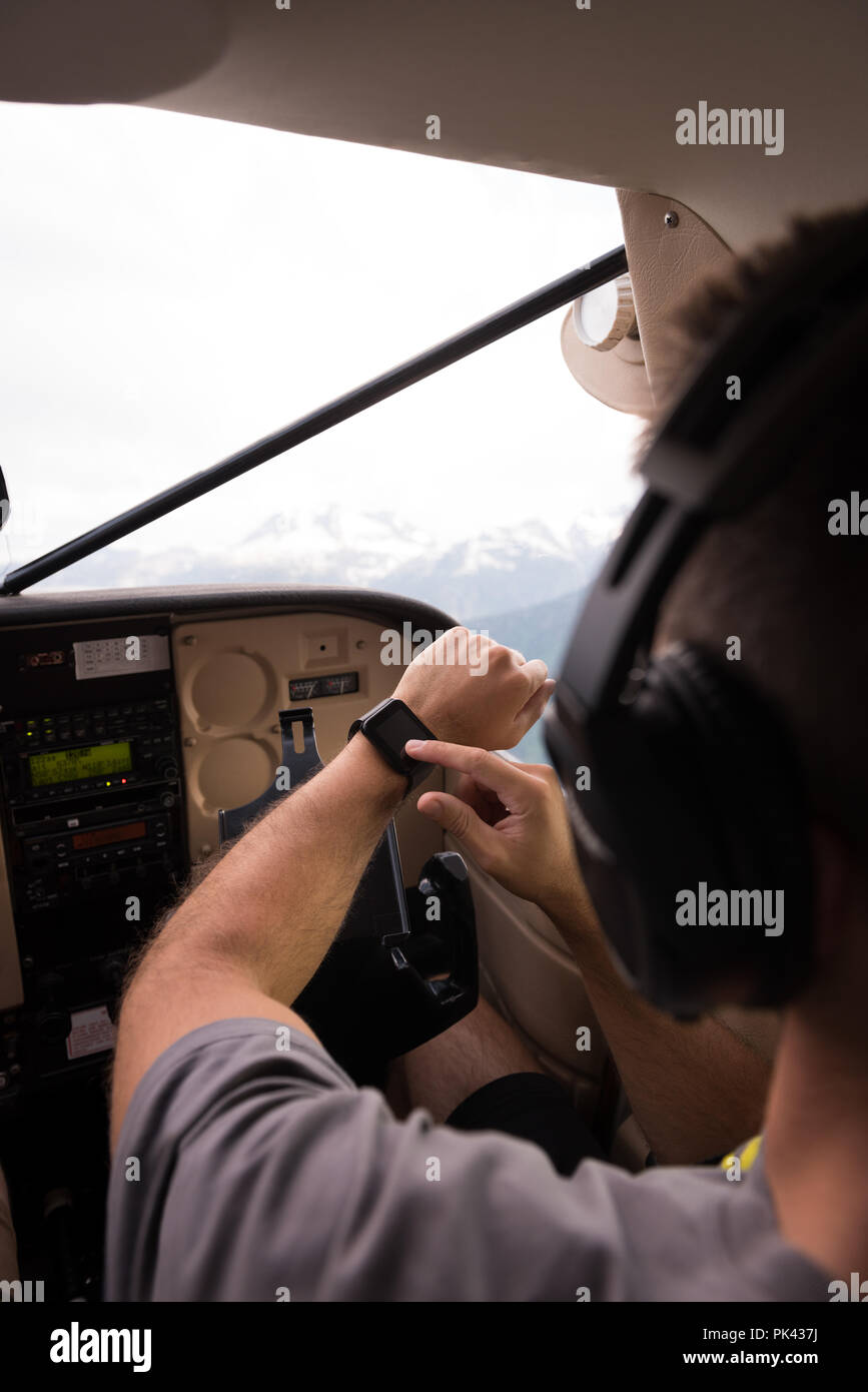 Pilot using smartwatch while flying - Stock Image