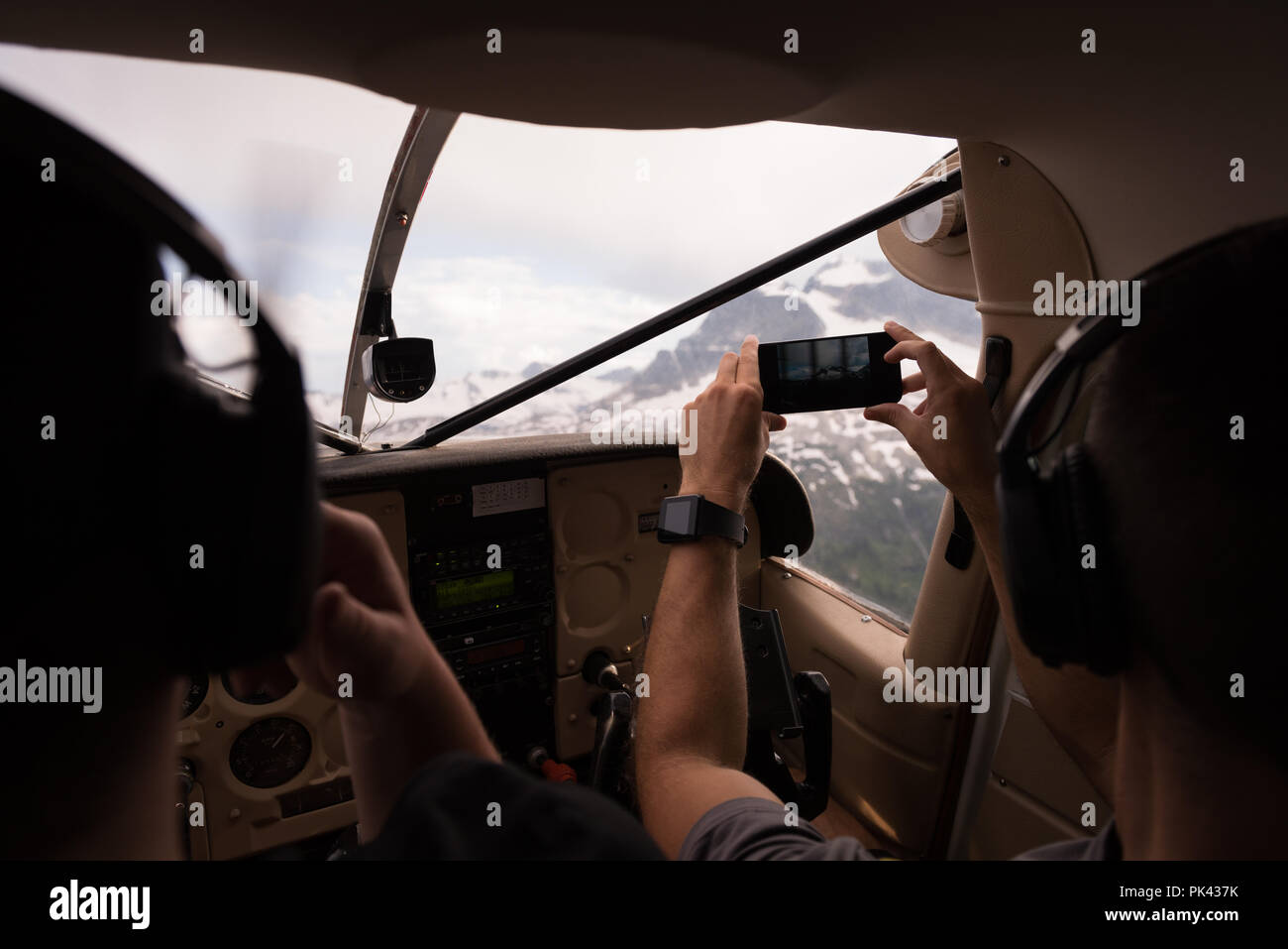 Pilot taking photos with mobile phone while flying - Stock Image