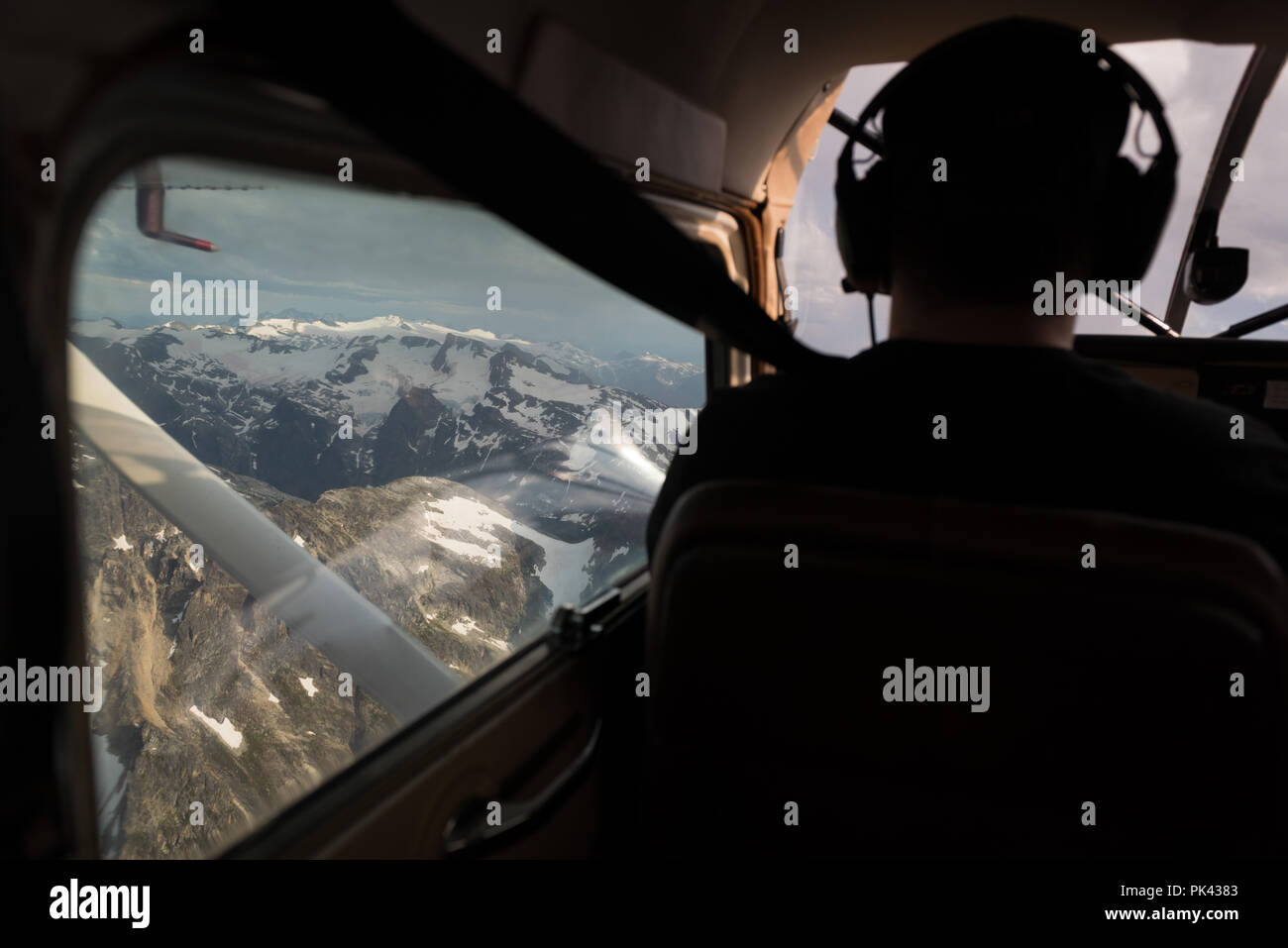 Pilot flying aircraft over snowcovered mountain - Stock Image