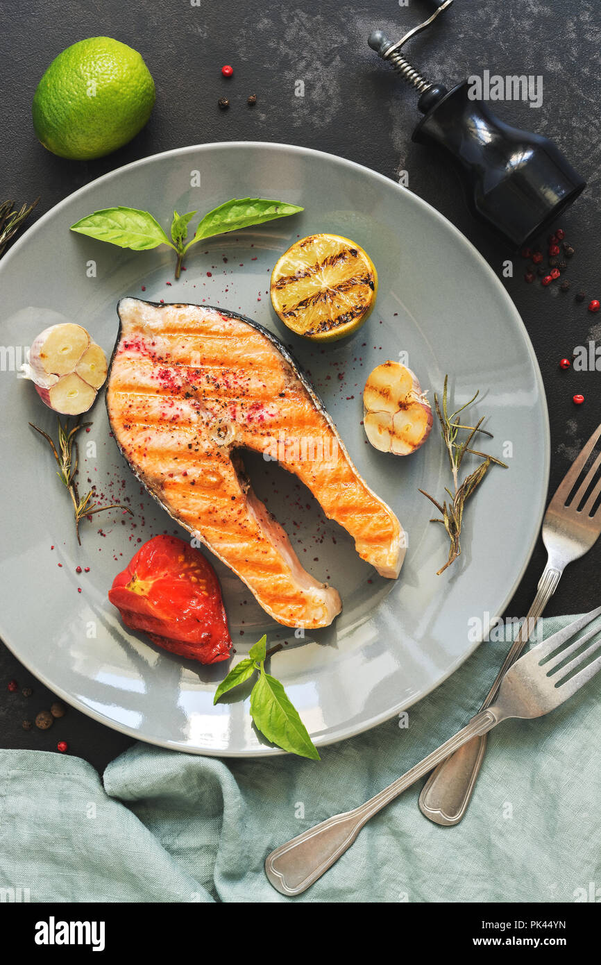 Grilled salmon steak served on a gray plate, black concrete background. Top view,flat lay - Stock Image