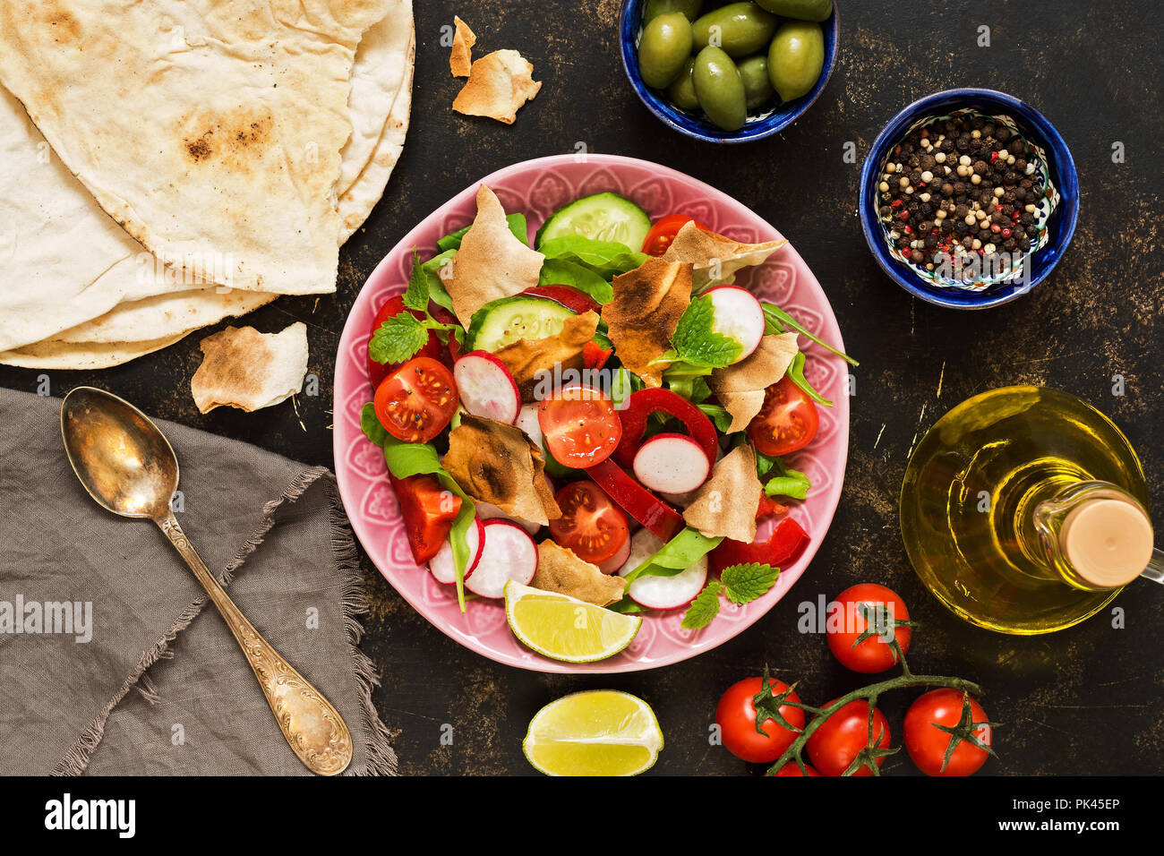 Arabic dish salad fattoush. Pita bread, tomatoes and seasonings. View from above - Stock Image