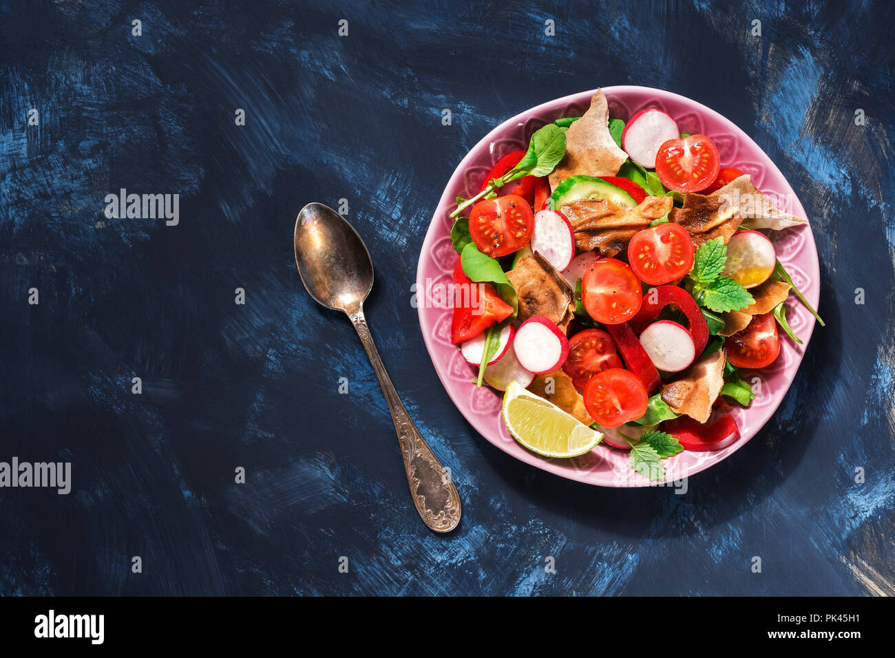 Arabic salad of fresh vegetables with bread Fattoush on a blue background. Top view, copy space. Stock Photo
