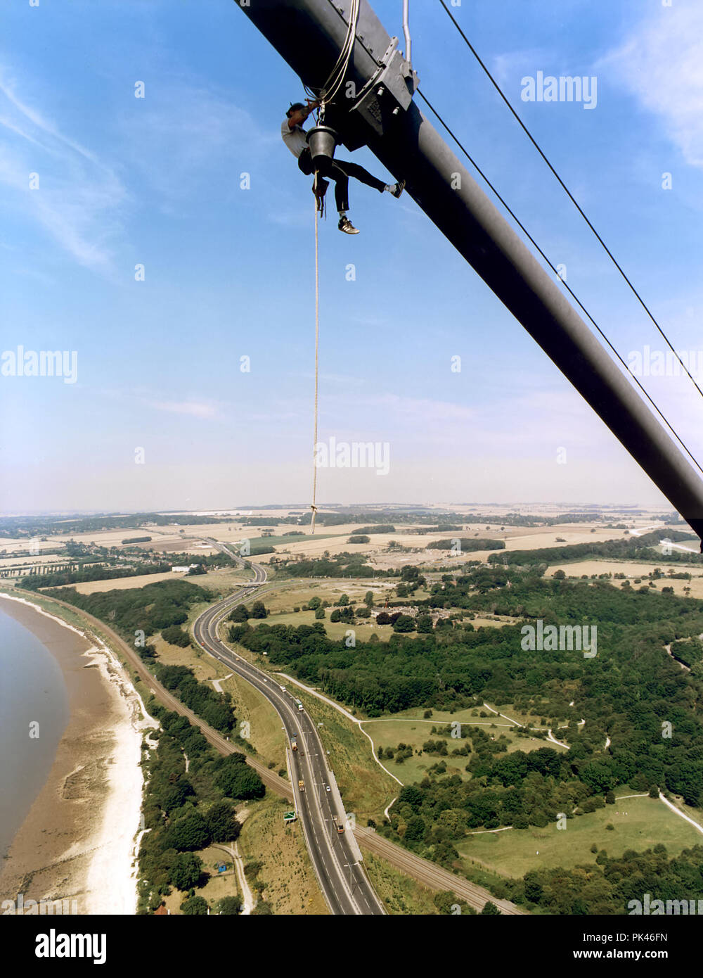 An abseiler checks the condition of the cables on the Humber Bridge - Stock Image