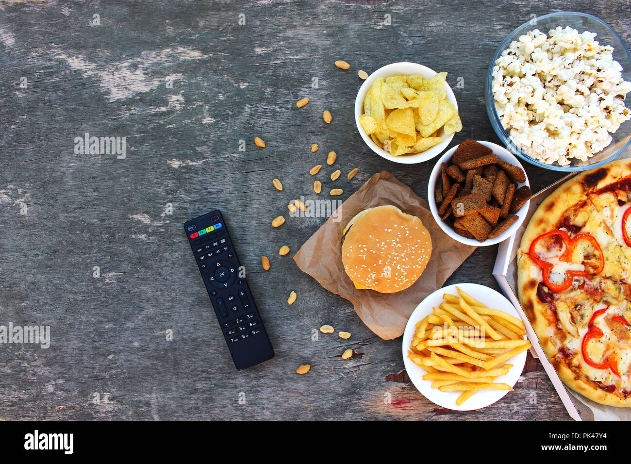 TV remote control, fast food on old wooden background. Concept of junk eating. Top view. Flat lay. - Stock Image