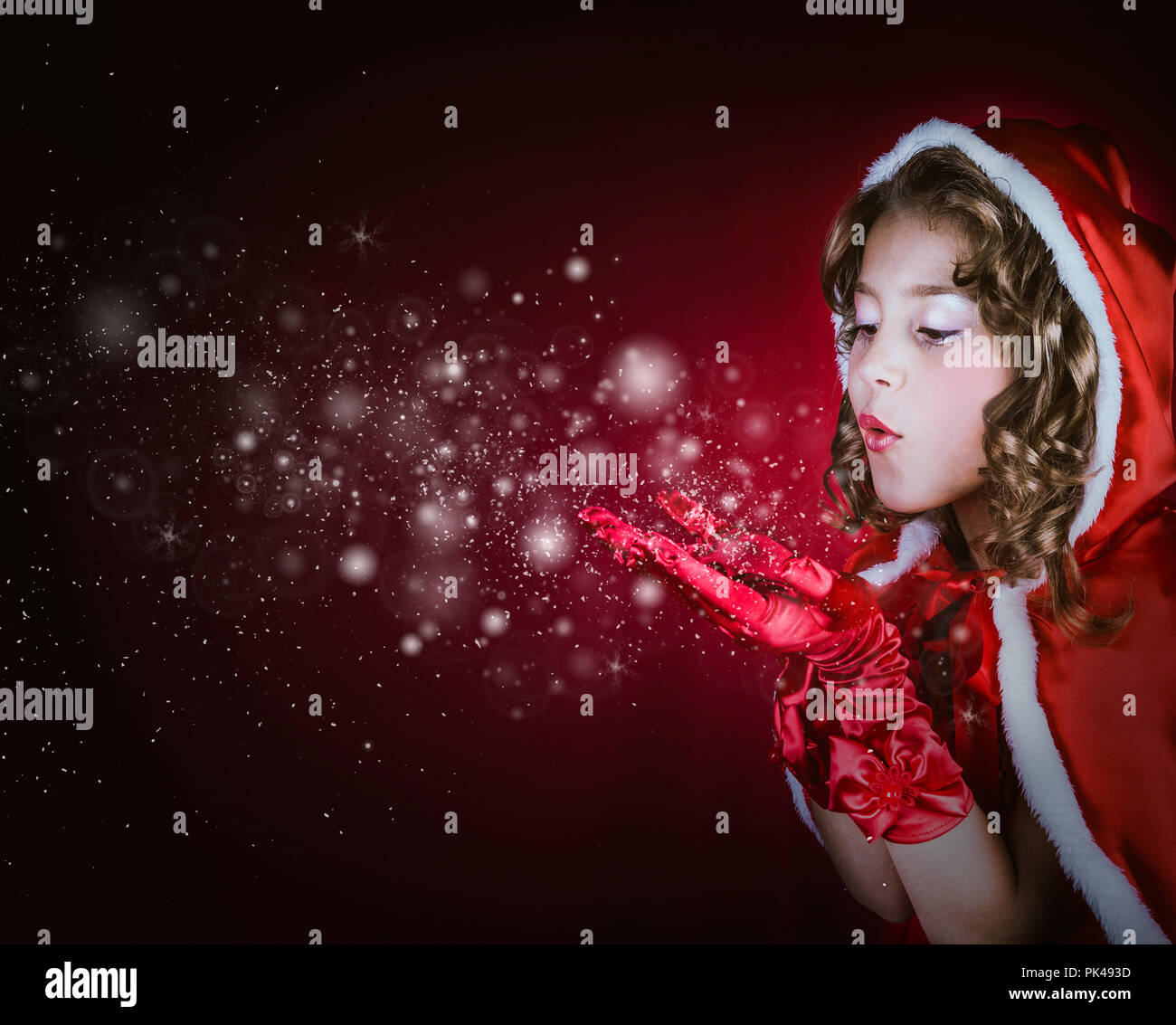 Christmas magic. Little girl wearing Santa Claus costume whispering snowflakes on a red background - Stock Image