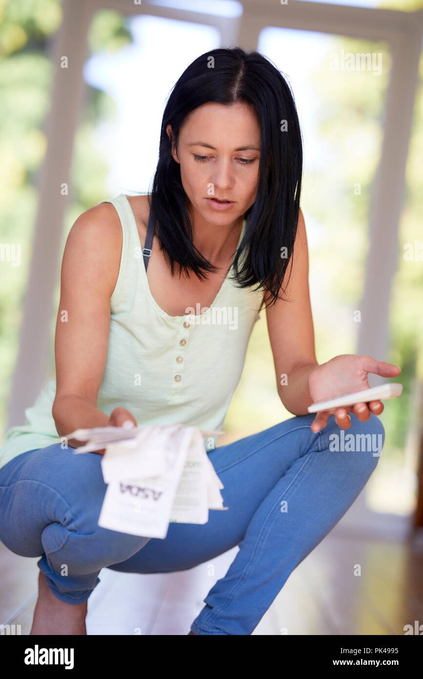 Woman looking at receipts - Stock Image