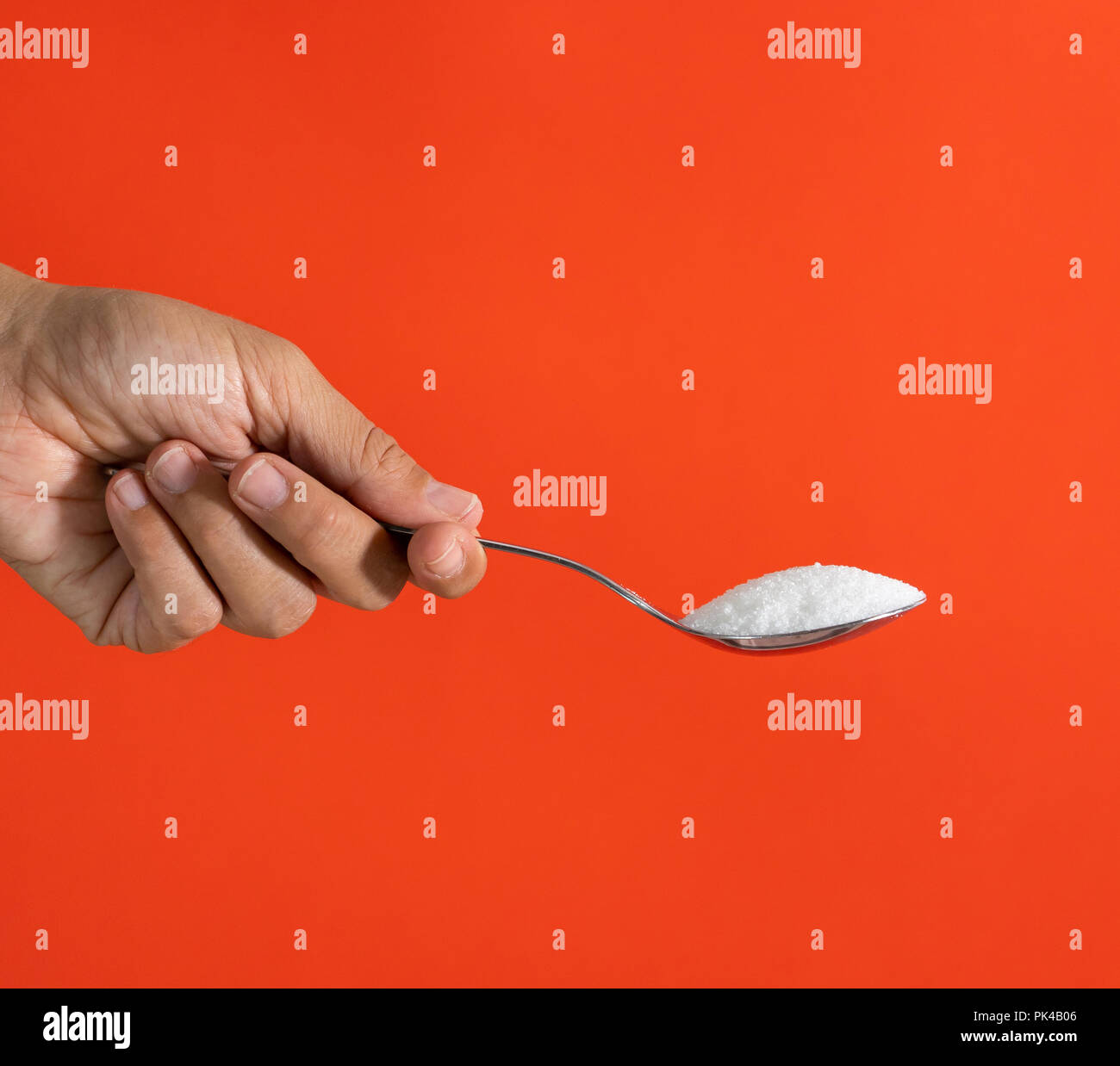 Woman hand holding and offering a spoon full of sugar isolated on a red background in sugar addiction, diet, health problems, diabetes, calories and q - Stock Image