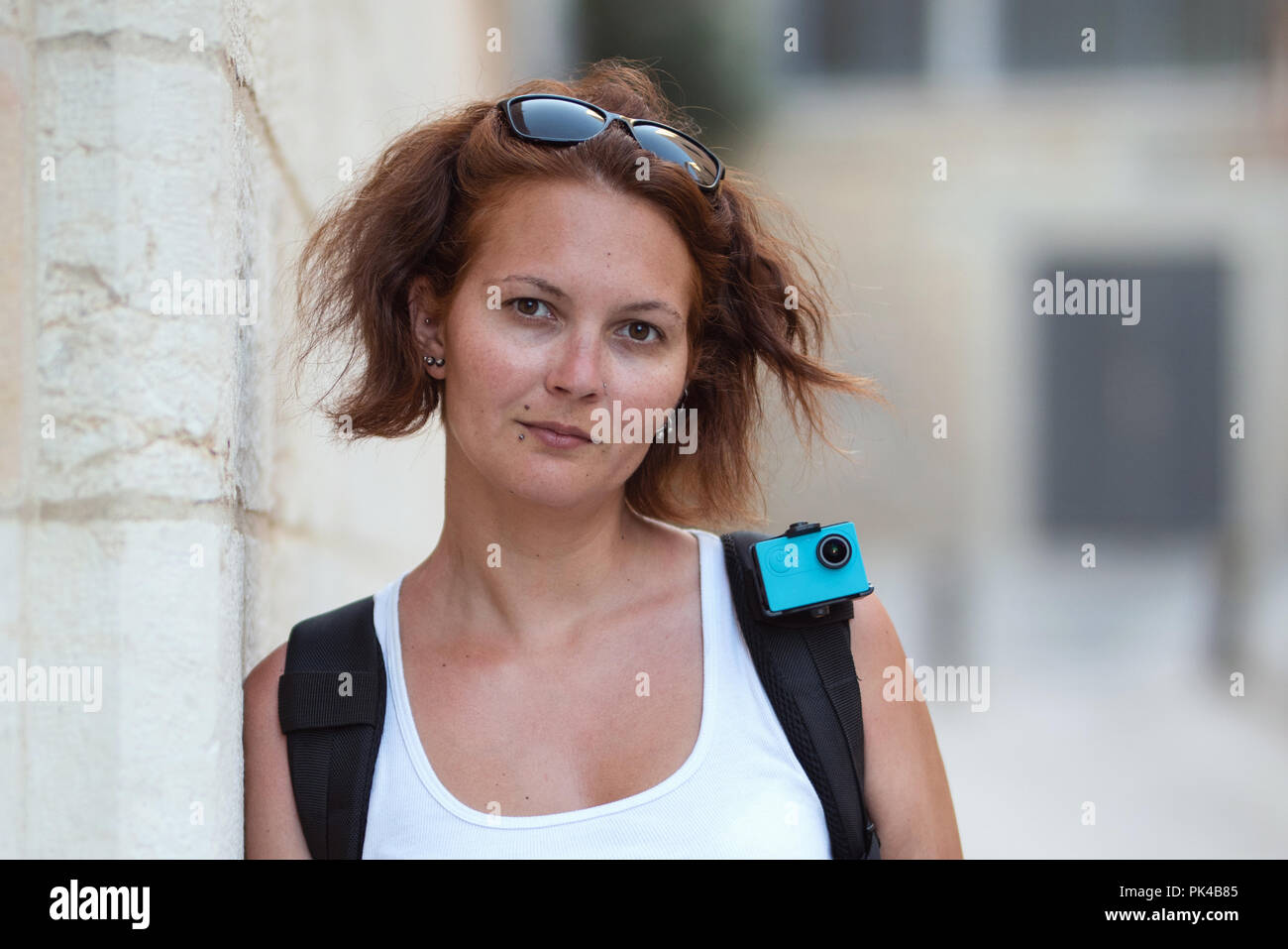 Portrait of redhead woman traveling with backpack and action camera Stock Photo