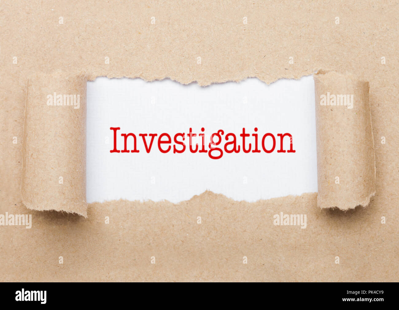 Investigation concept text appearing behind torn brown paper envelope Stock Photo