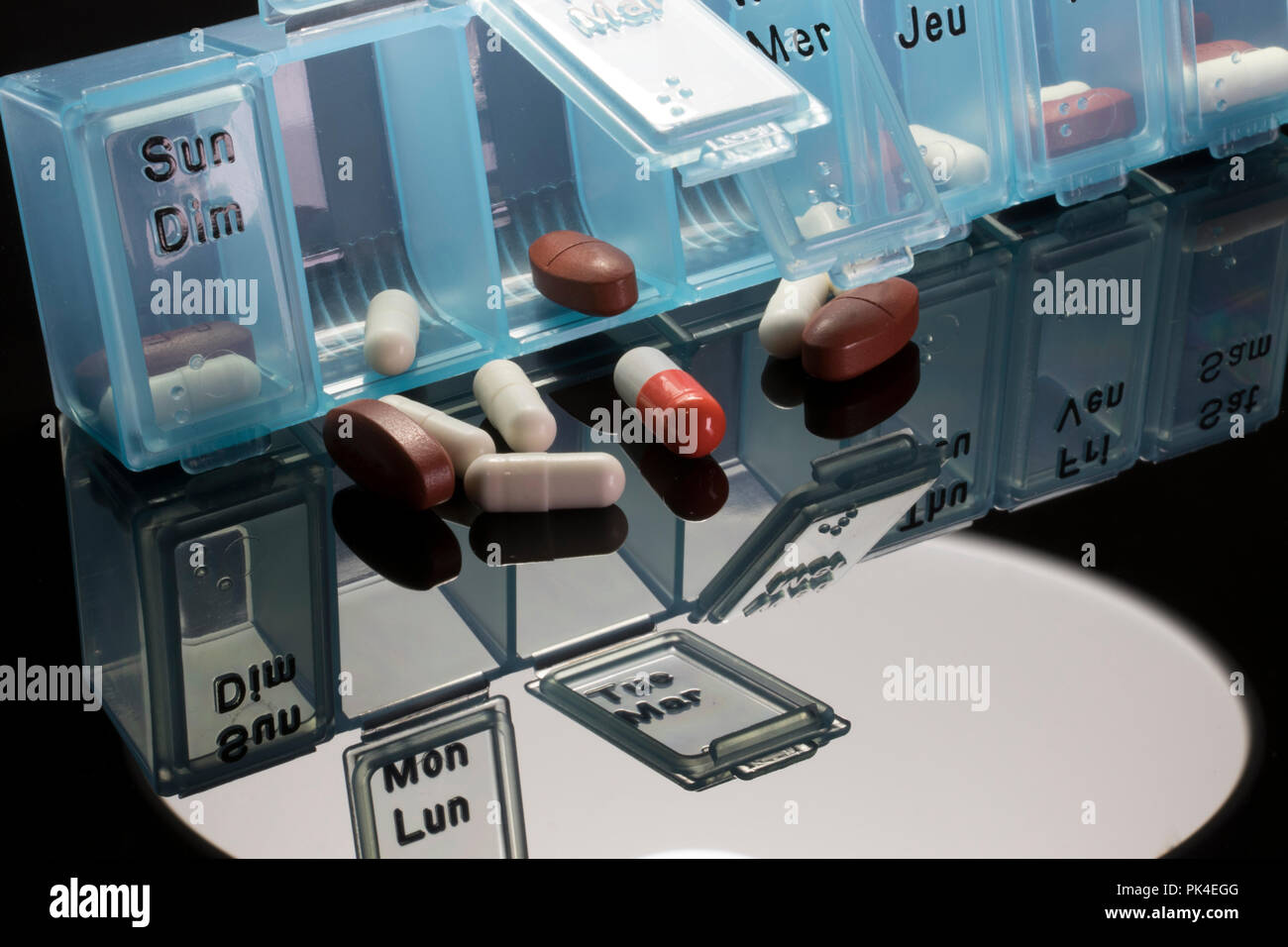 Blue pill dispenser with vitamins, pills and capsules. Concept of helth amd medical care. - Stock Image