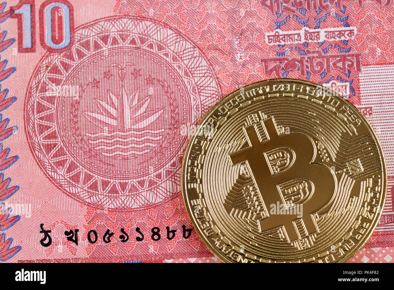 Close up image of a red, ten taka Bangladeshi note with a golden bitcoin - Stock Image