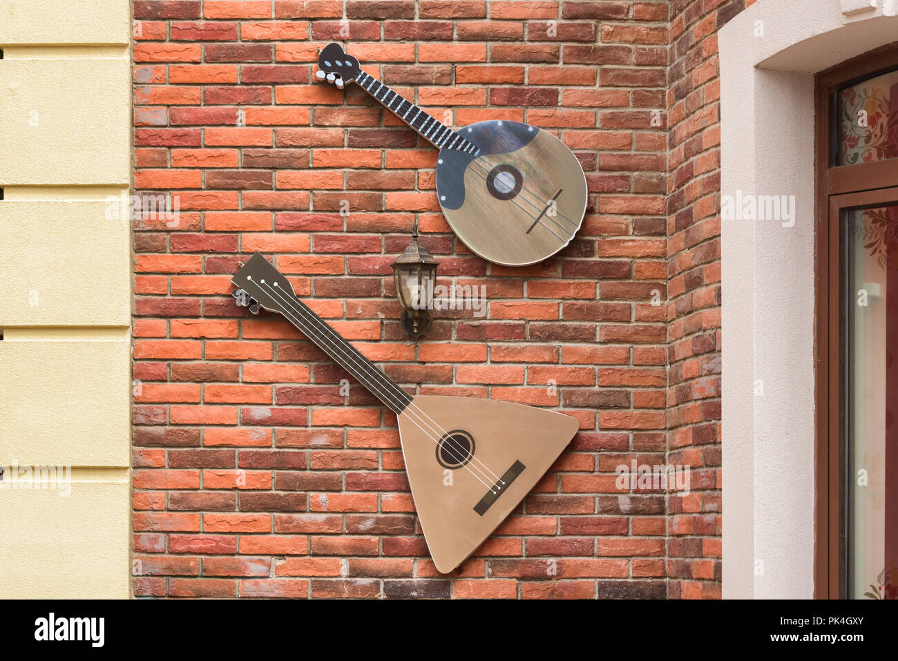 Musical instrument balalaika on the wall. Scenery on the wall of the building - Stock Image