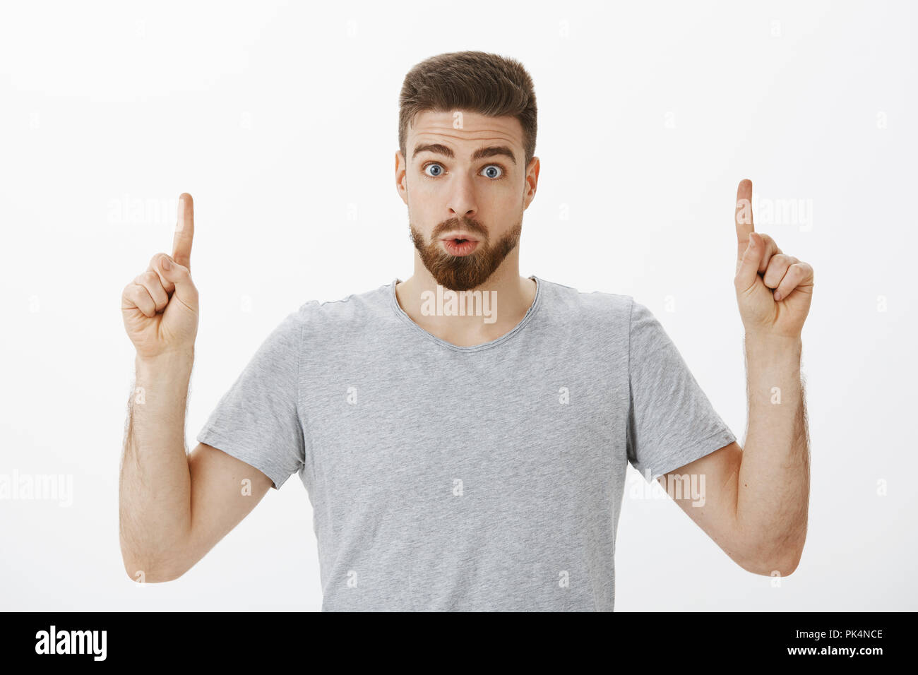 Indoor shot of interested and intrigued handsome masculine man with beard and brown hairstyle folding lips from amazement and curiosity raising index fingers pointing up questioned over gray wall - Stock Image