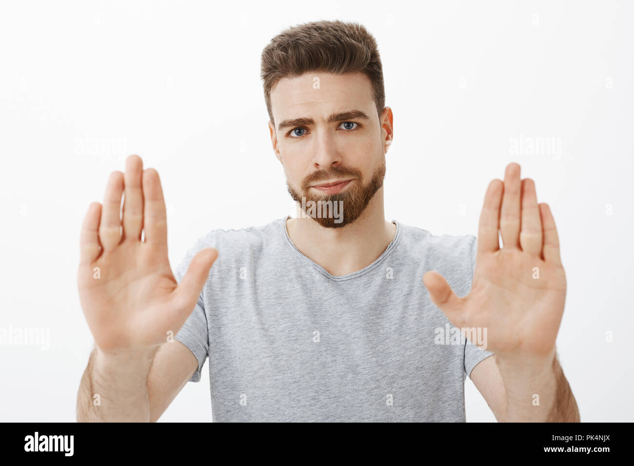 Enough I fed up. Portrait of pressured and displeased masculine and handsome caucasian man with beard and blue eyes raising palms in stop gesture smirking from dislike giving refusal over gray wall - Stock Image