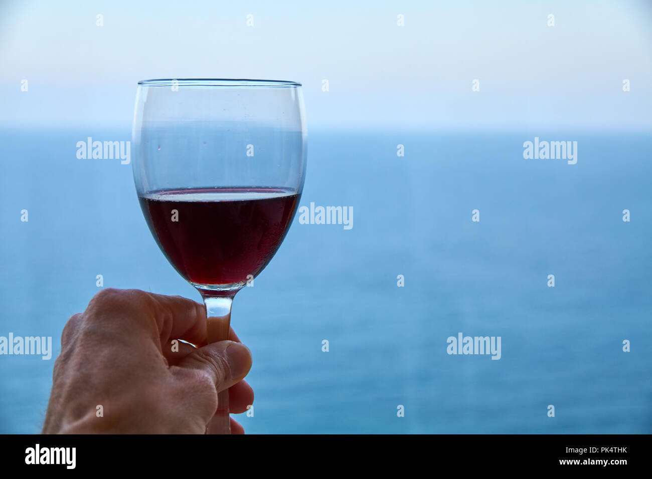 hand grabing a glass of wine in front of the swa Stock Photo