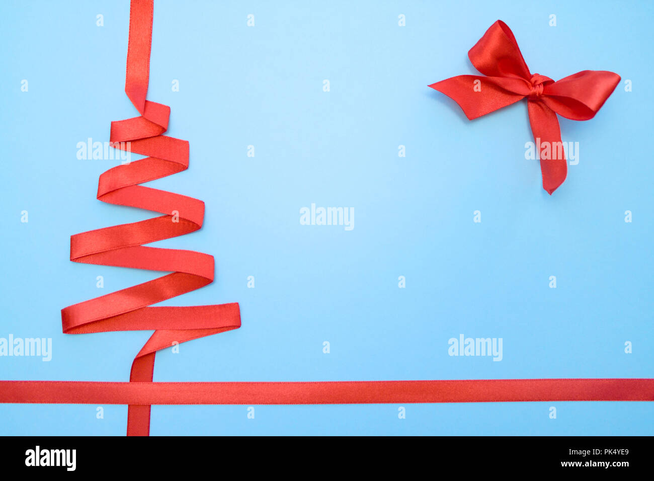 holidays winter and celebration concept christmas and new year tree made from red ribbon on blue background free space for text