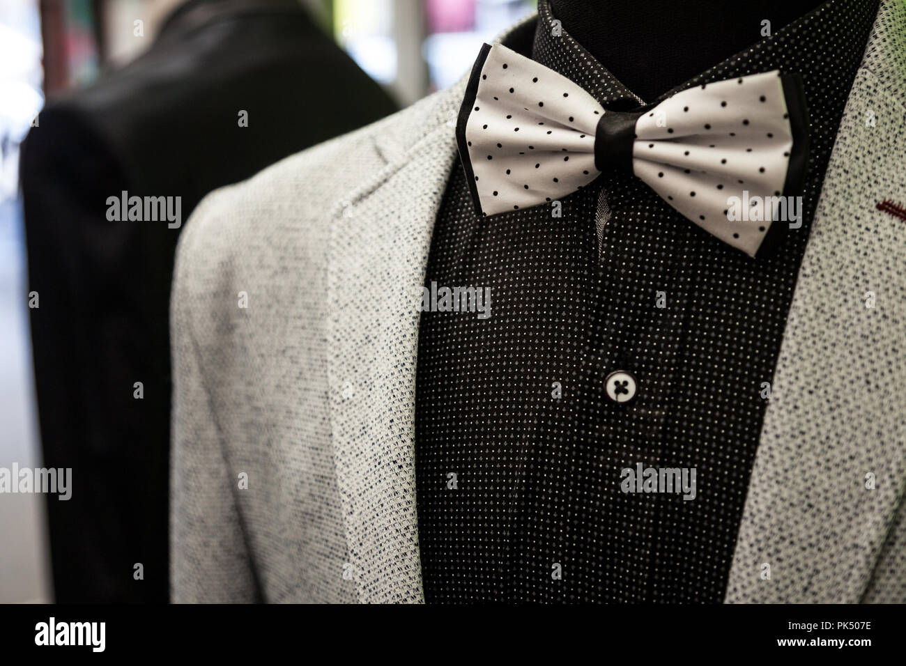 White bowtie with black dots, on display with a black shirt and a white wool suit jacket. Bow ties are a symbol of elegance and style, currently back  - Stock Image