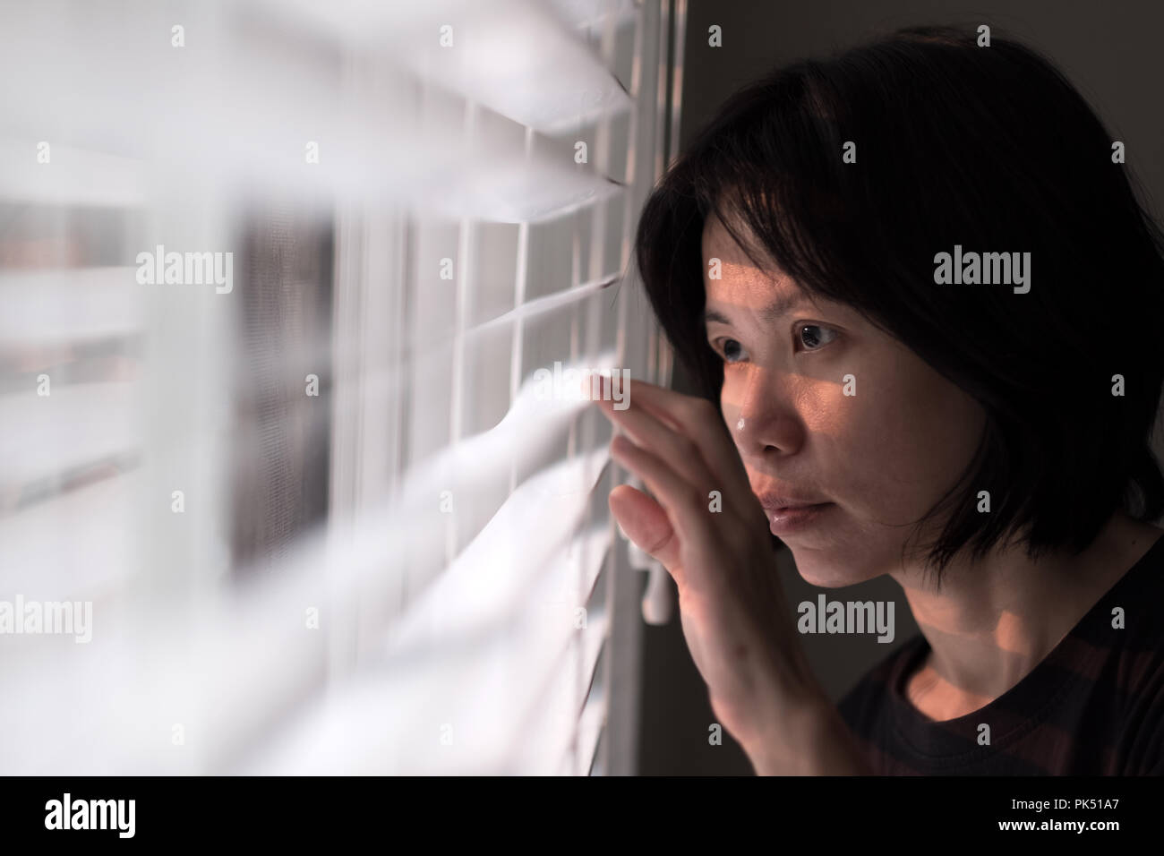 Portrait of young Asian woman peeking out of window Stock Photo
