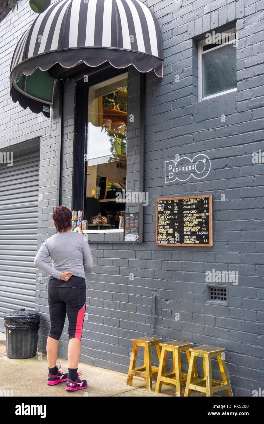 A woman wearing sportswear purchasing a coffee from a coffee shop window, Perth WA Australia. - Stock Image