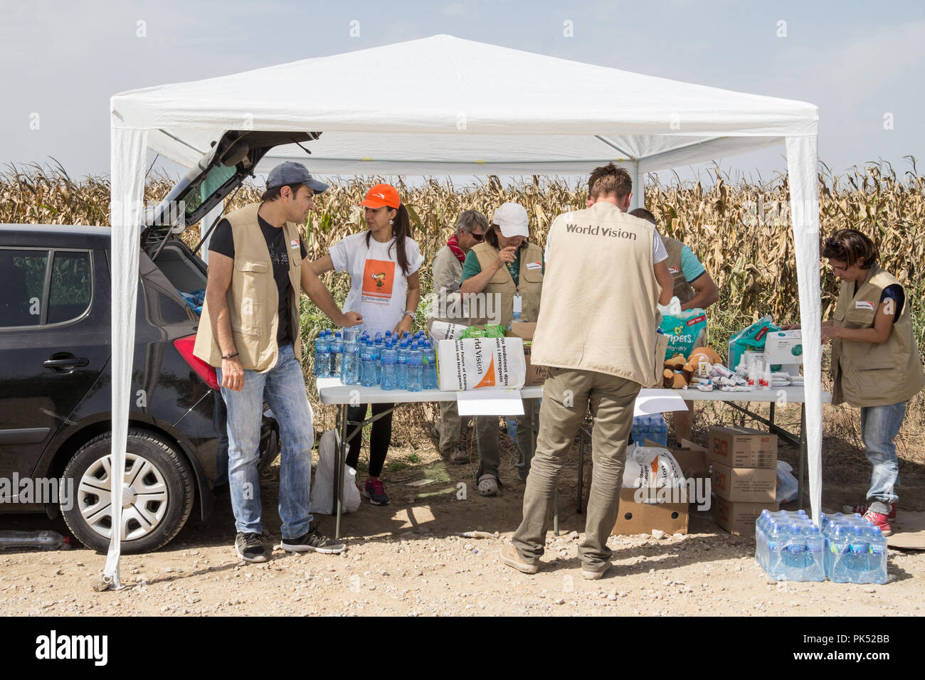 TOVARNIK, CROATIA - SEPTEMBER 19, 2015: Workers of the NGO World Vision provinding aid to refugees at the border between Serbia and Croatia, on the Ba - Stock Image