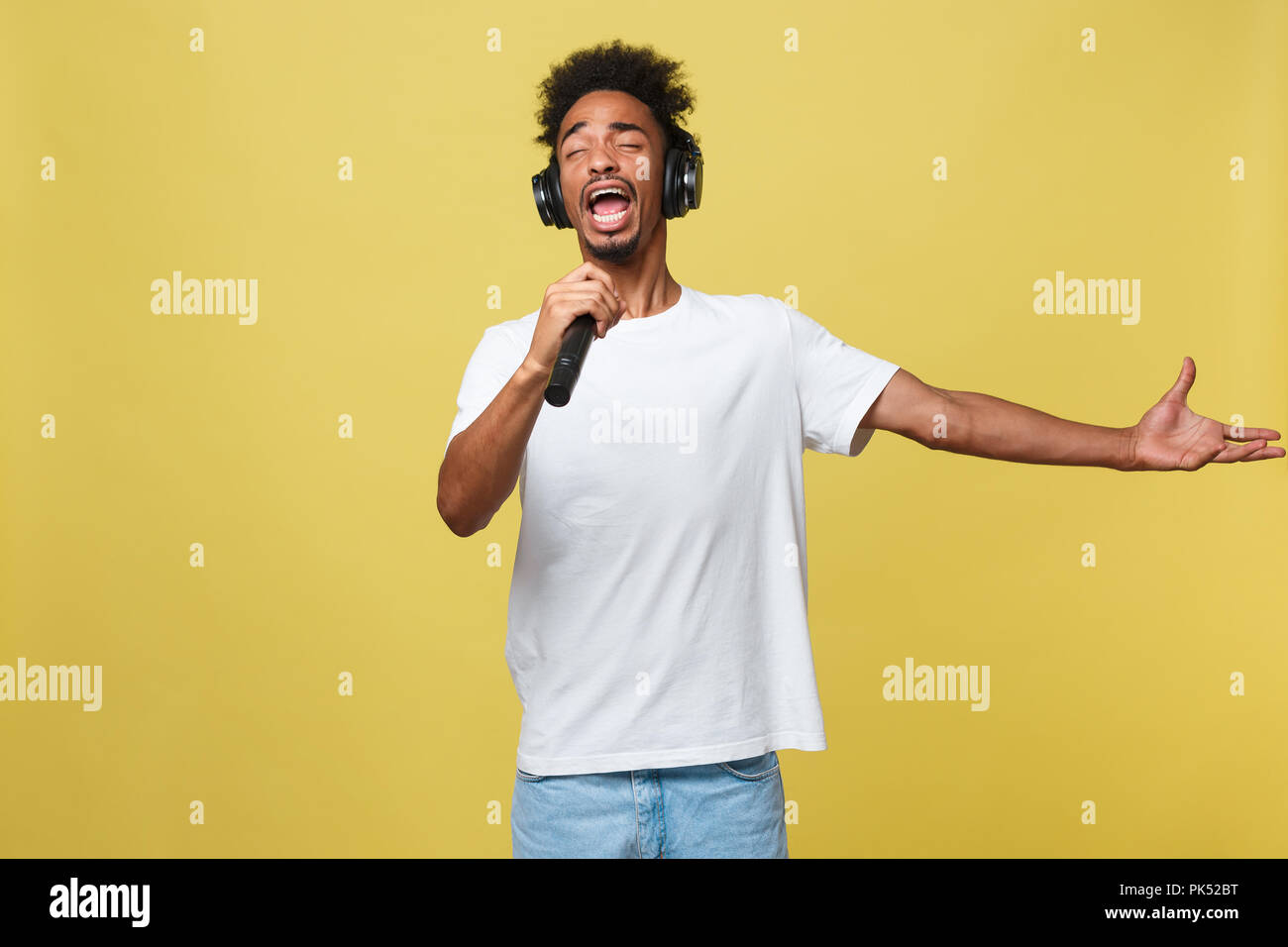 young handsome african american boy singing opera emotional with microphone. Stock Photo