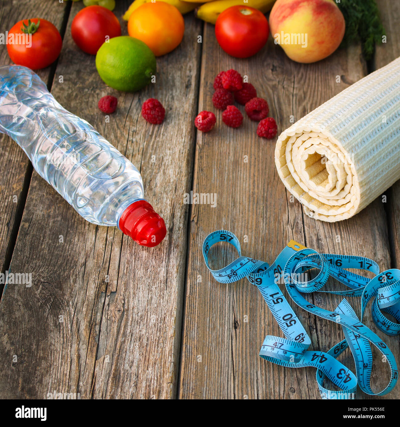 Fruits, vegetables, water, measurement tape and sports goods on wooden background. - Stock Image