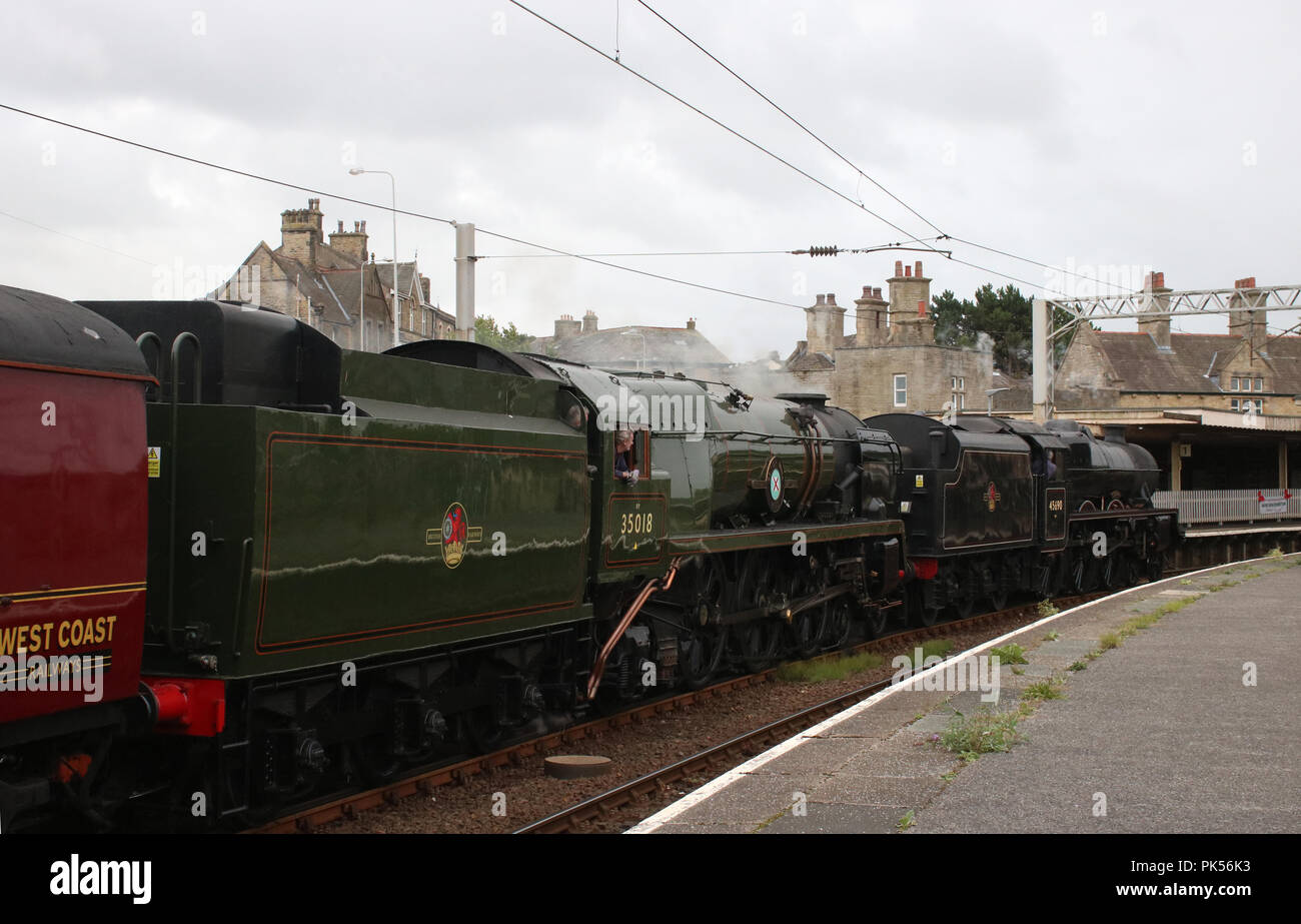 Preserved Jubilee class steam locomotive 45690 Leander arriving at Carnforth railway station with 35018 British India Line on 10th September 2018. - Stock Image