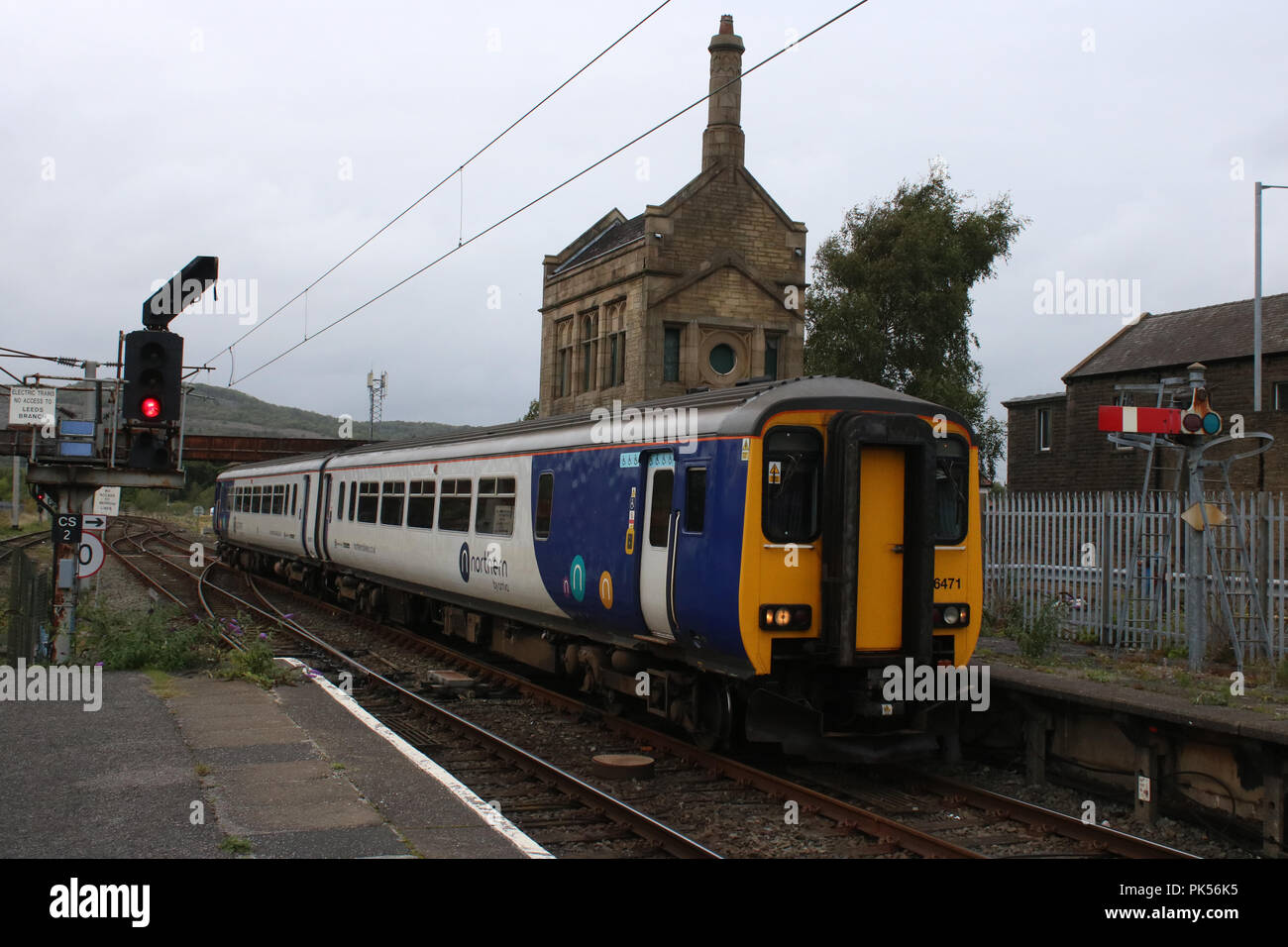 Class 156 two car diesel multiple unit train in Northern livery arriving at Carnforth railway station with a passenger service to Lancaster. - Stock Image