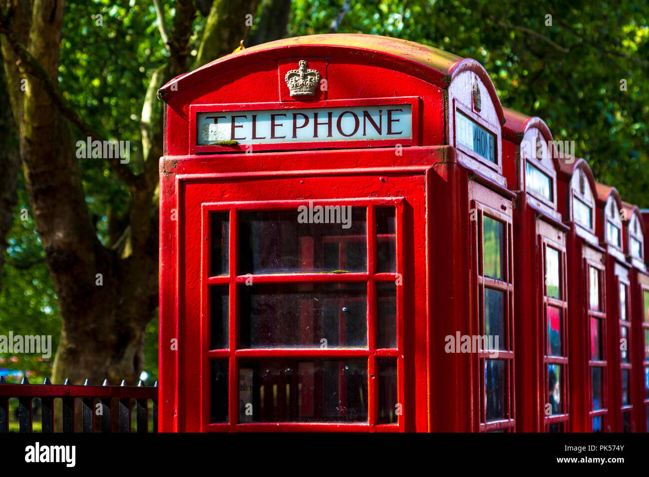 Row of iconic red K6 London telephone boxes near Hyde Park, London, symbol in the UK - Stock Image