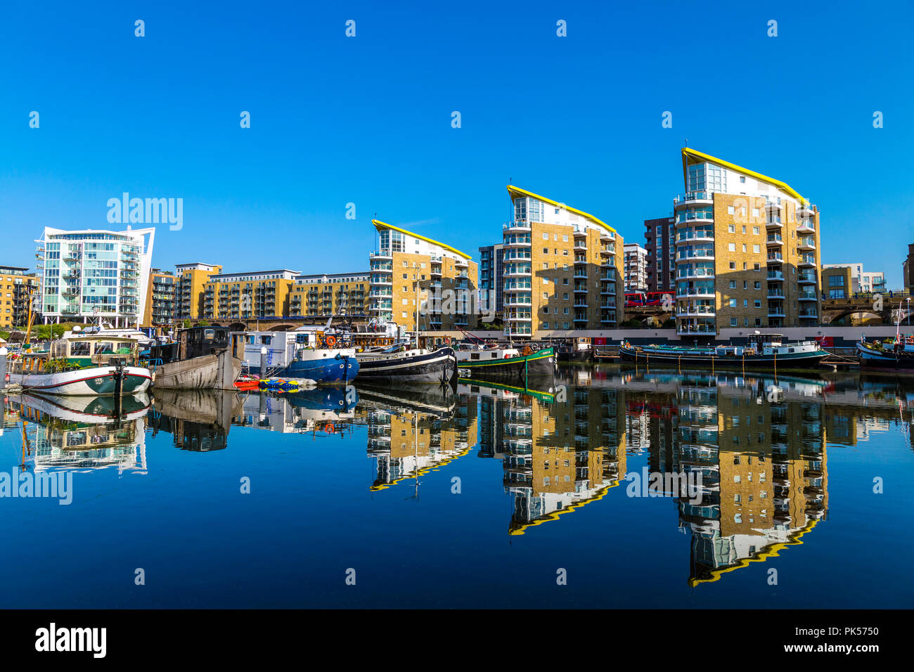 Houseboats and narrowboats mooring in the Limehouse Marina on a sunny day, London, UK - Stock Image
