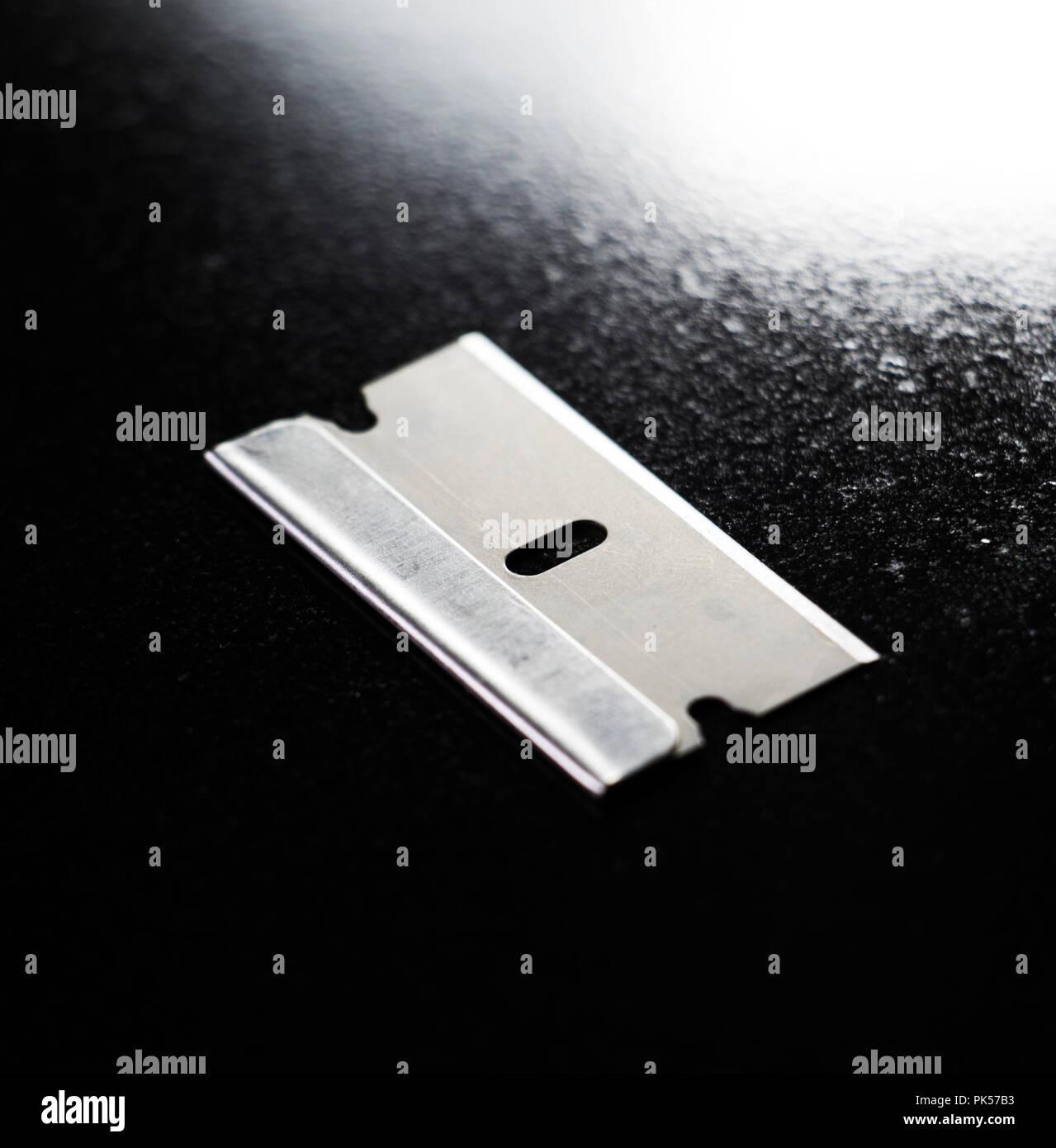 Razor blade isolated on black shinny background. - Stock Image