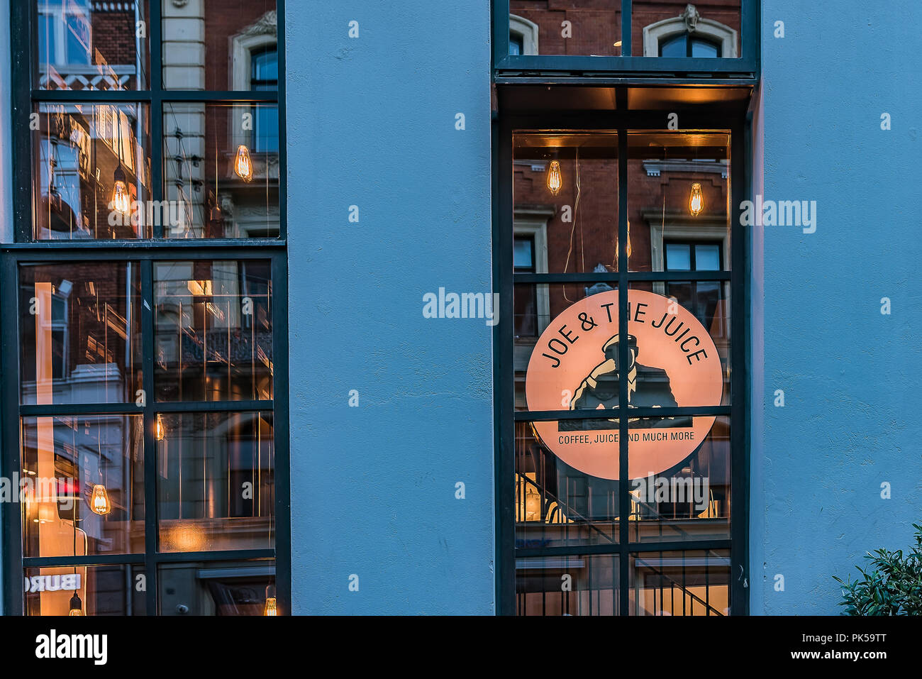 Reflections at night in the windows of the coffe-shop Joe & the juice in Copenhagen, September 6, 2018 - Stock Image
