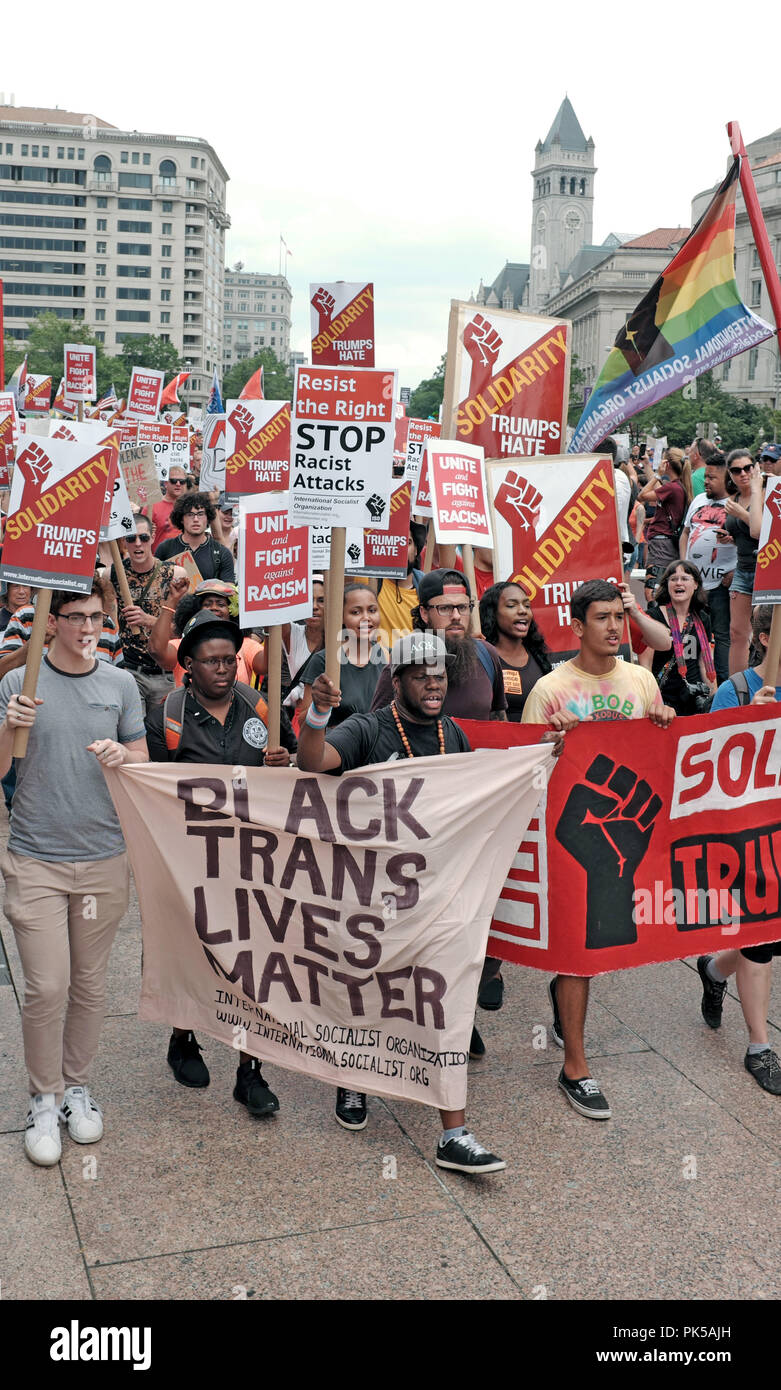 Street protestors against hate, bigotry and racism hold a banner 'Black Trans Lives Matter' and signs stating 'Solidarity Trumps Hate'. - Stock Image