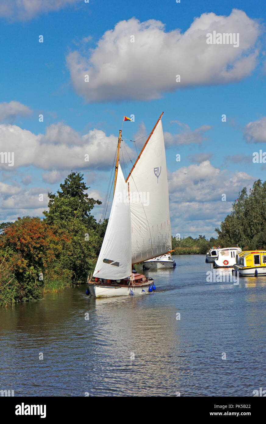 A yacht in full sail with motor cruisers on the River Ant on the Norfolk Broads by How Hill, Ludham, Norfolk, England, United Kingdom, Europe. - Stock Image
