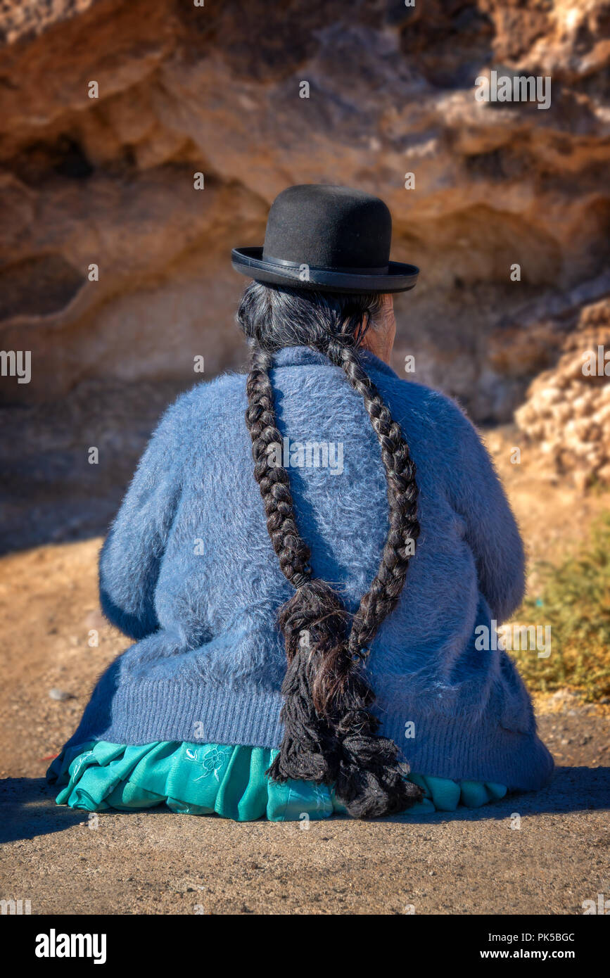 Old bolivian woman in traditional outfit with a hat and long braids - Stock Image