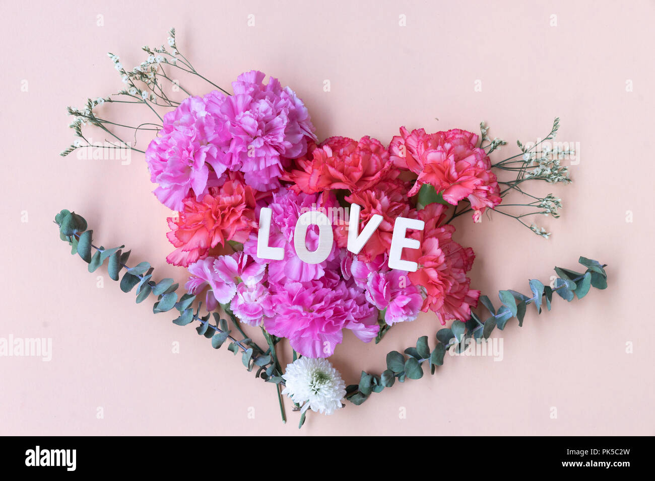 Love Wooden Word On Fresh Carnation Flowers Bouquet Stock Photo
