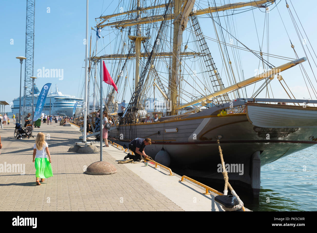 Child harbor ship, rear view of a small child in a green skirt walking beside a 19th Century sailing ship in Tallinn harbor on a summer day, Estonia. Stock Photo