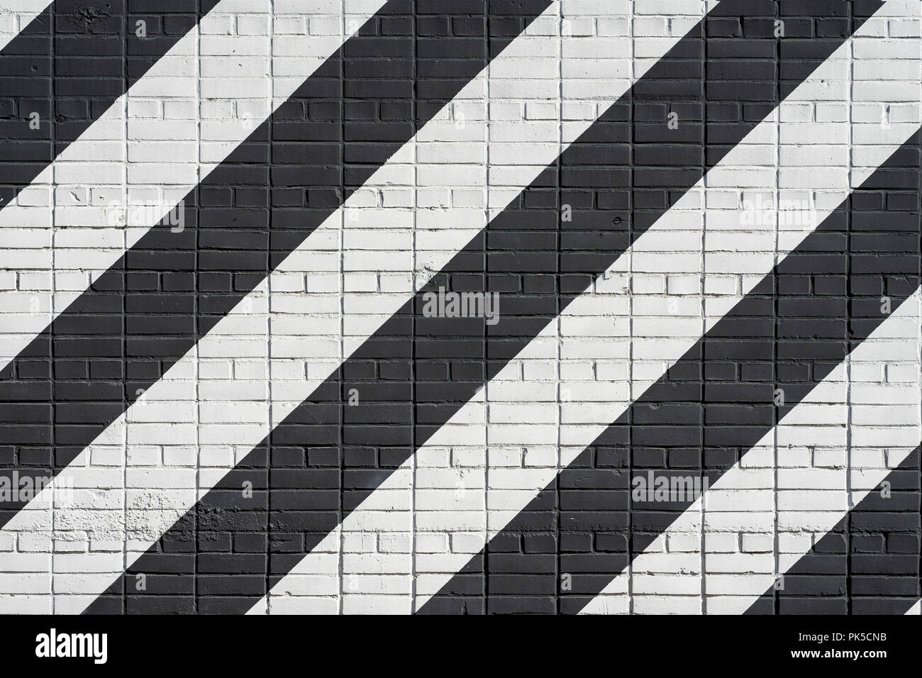 Diagonally painted Black and white bricks wall . Graphic grunge texture of surface, as graffiti. Abstract modern background - Stock Image