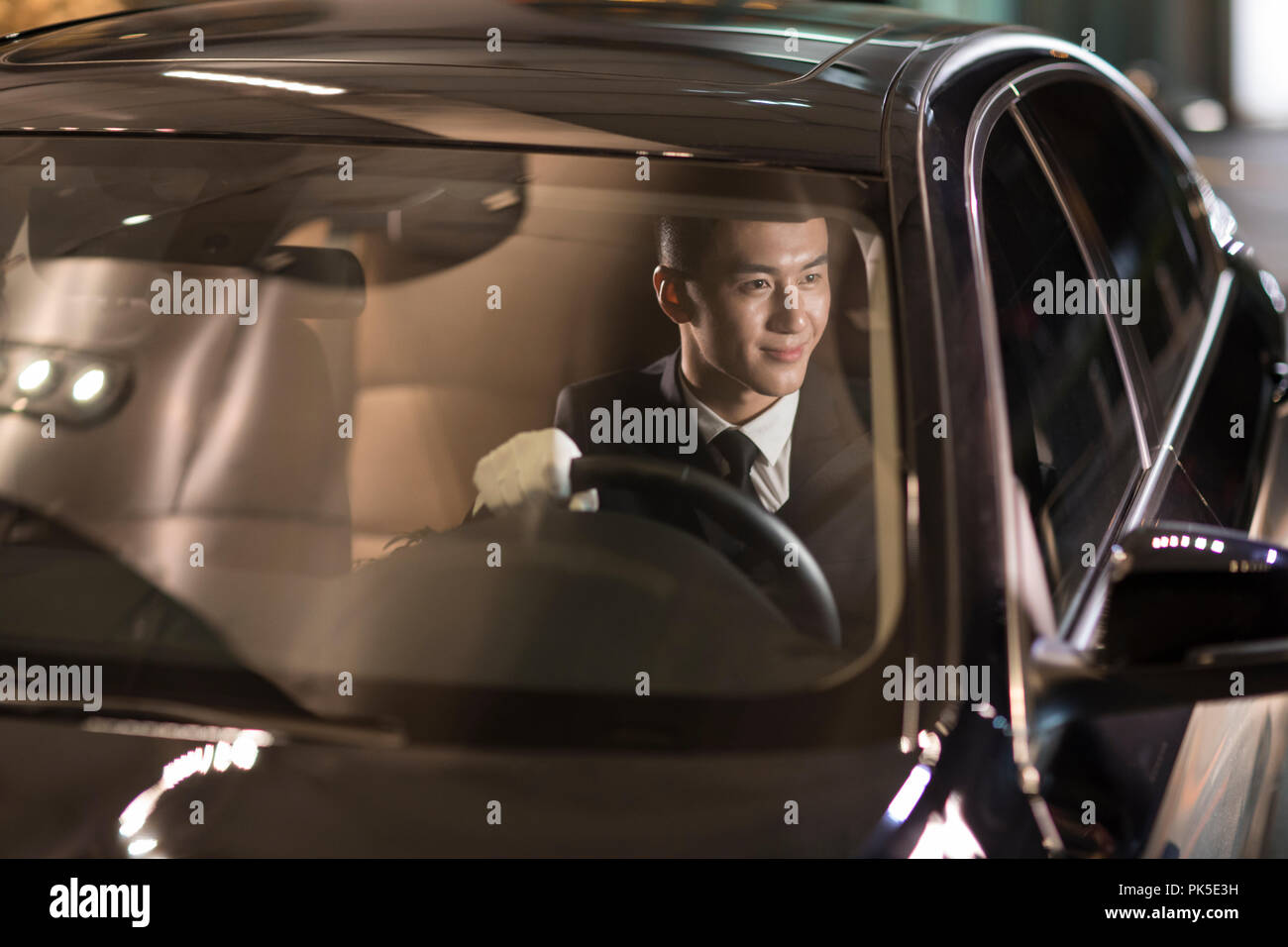 Cheerful chauffeur driving car - Stock Image