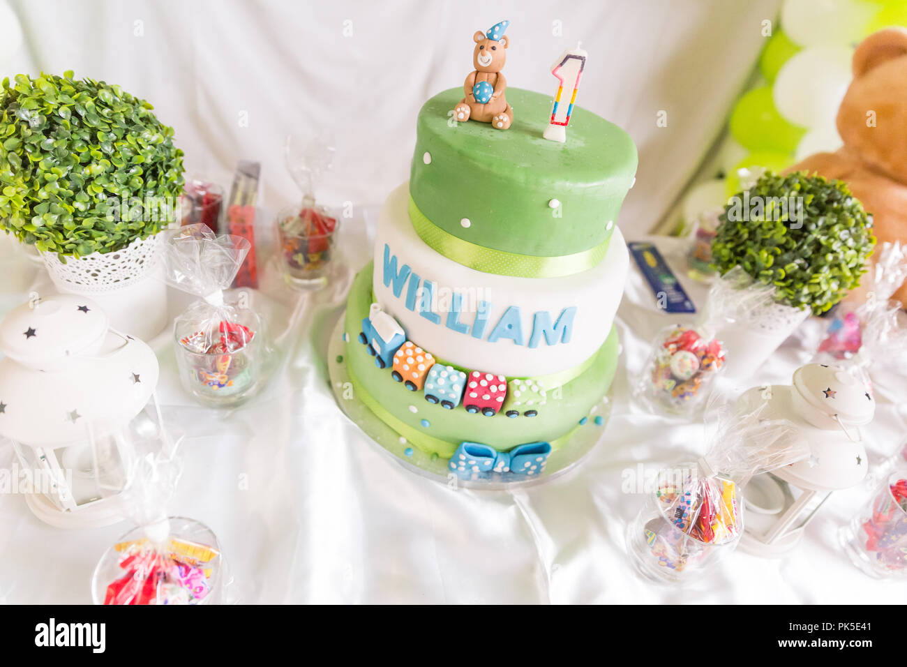 Green And White Birthday Cake With One Year Old Candle Teddy Bear On Table