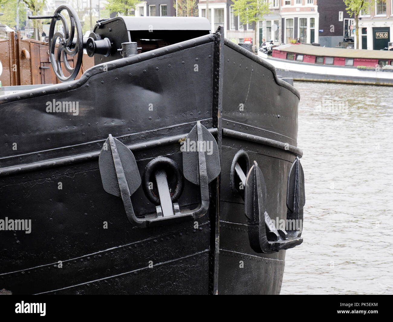 Bow of a traditional steel hulled Dutch barge with twin anchors moored on an Amsterdam canal. Stock Photo