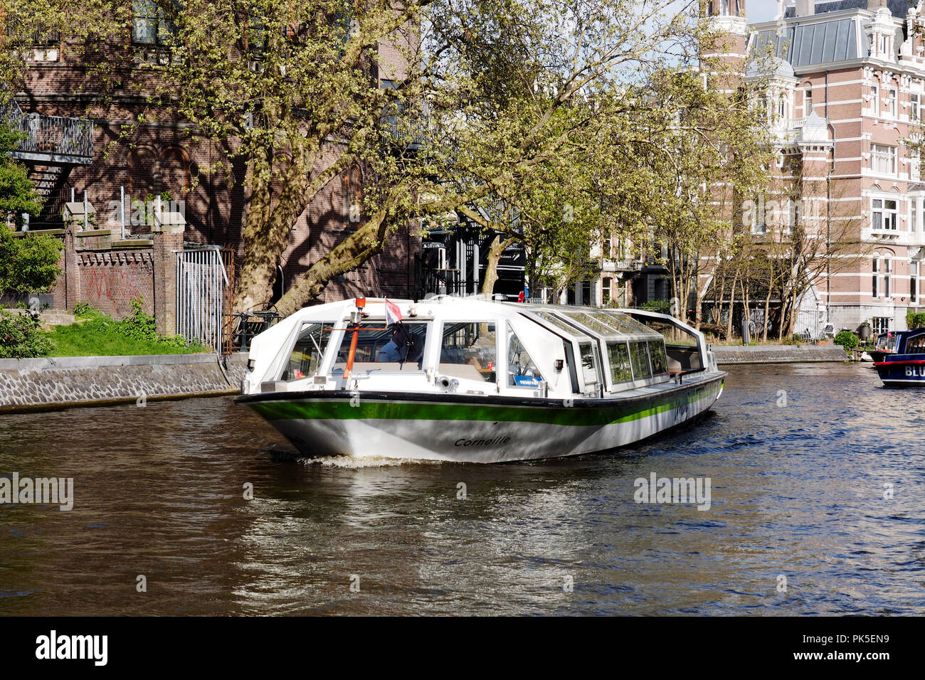 Amsterdam canal scene with large tour boats on the main canal by Stadhouderskade. These boats provide trips along the canals and harbour for tourists. Stock Photo