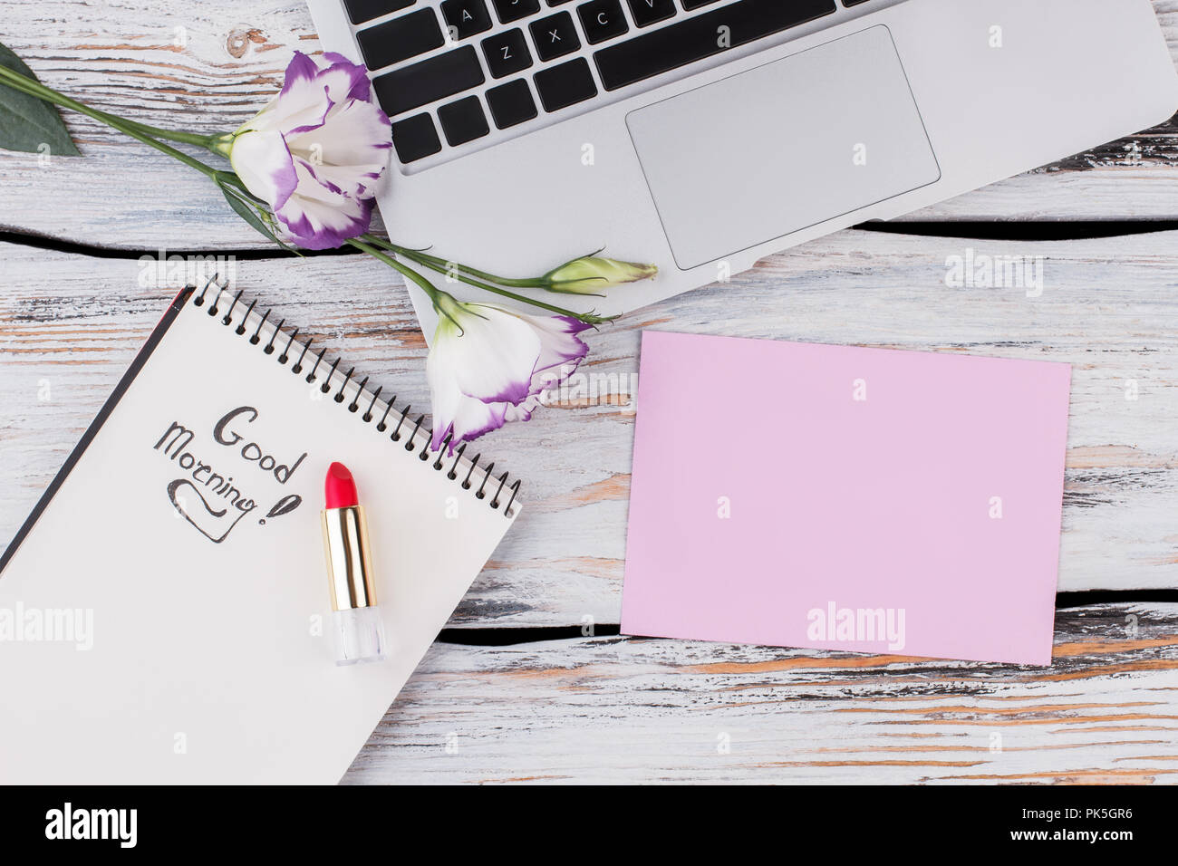 Top View Of Blank Paper Flowers Laptop And Lipstick Flat Lay