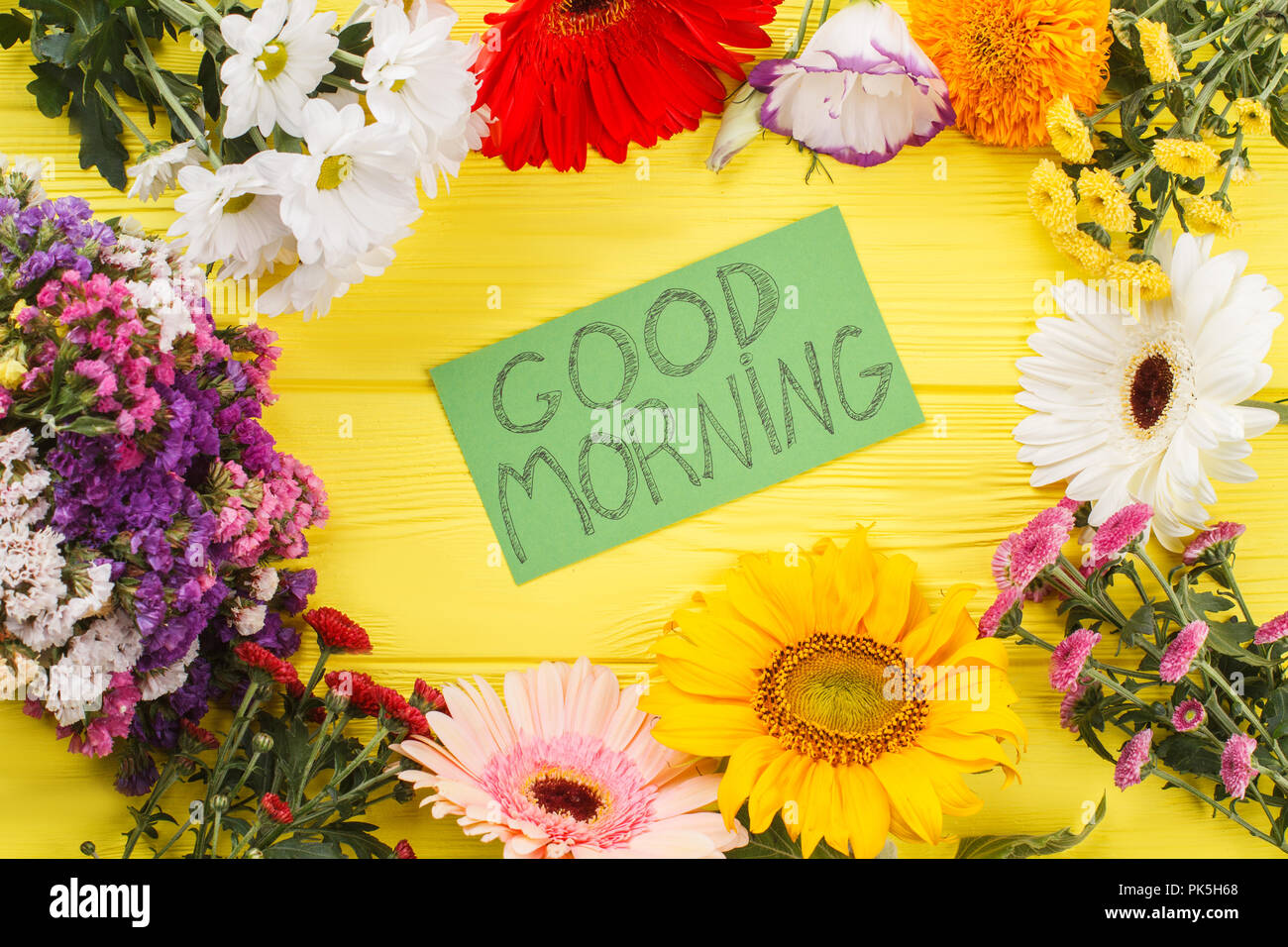 Lovely good morning wish and flowers yellow wooden desk background lovely good morning wish and flowers yellow wooden desk background mightylinksfo