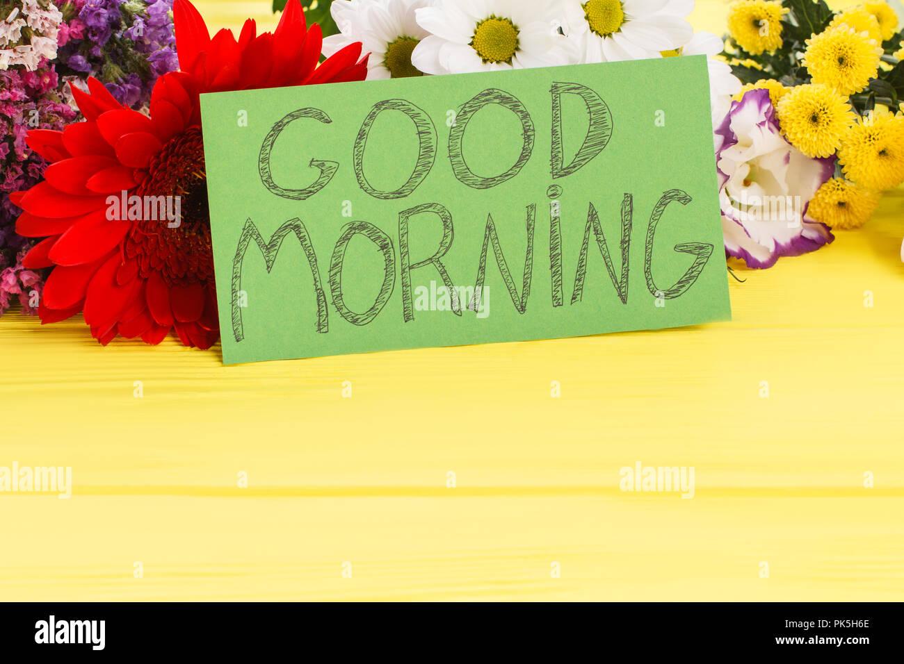 Good morning wish note and beautiful flowers close up yellow good morning wish note and beautiful flowers close up yellow wooden desk background izmirmasajfo