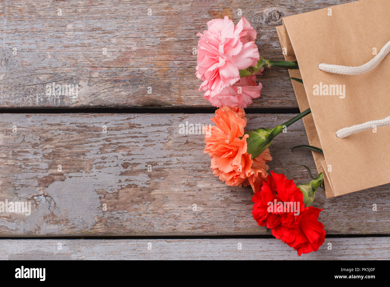 Different colorful carnation flowers in paper bag copyspace old different colorful carnation flowers in paper bag copyspace old wooden table background mightylinksfo
