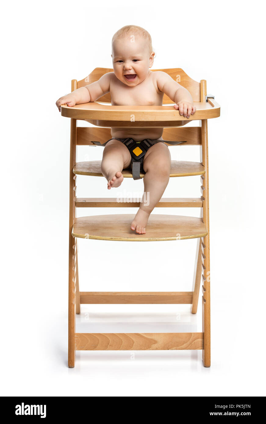 Happy cute baby girl sitting in high chair over white background - Stock Image