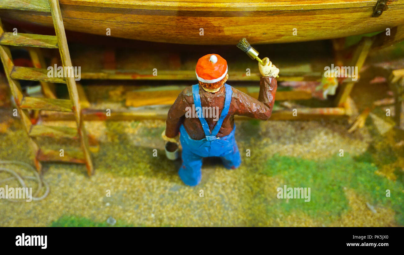 Miniature mini figure worker painting a boat at dock diorama - Stock Image