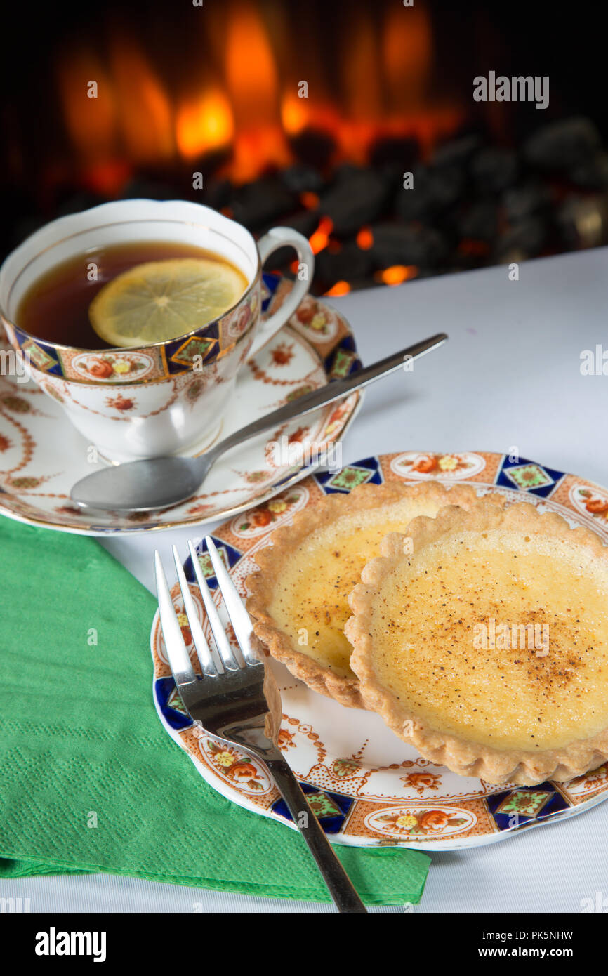 An English high tea of homemade Custard tart with lemon tea served on Roslyn bone China 8508 tea service - Stock Image