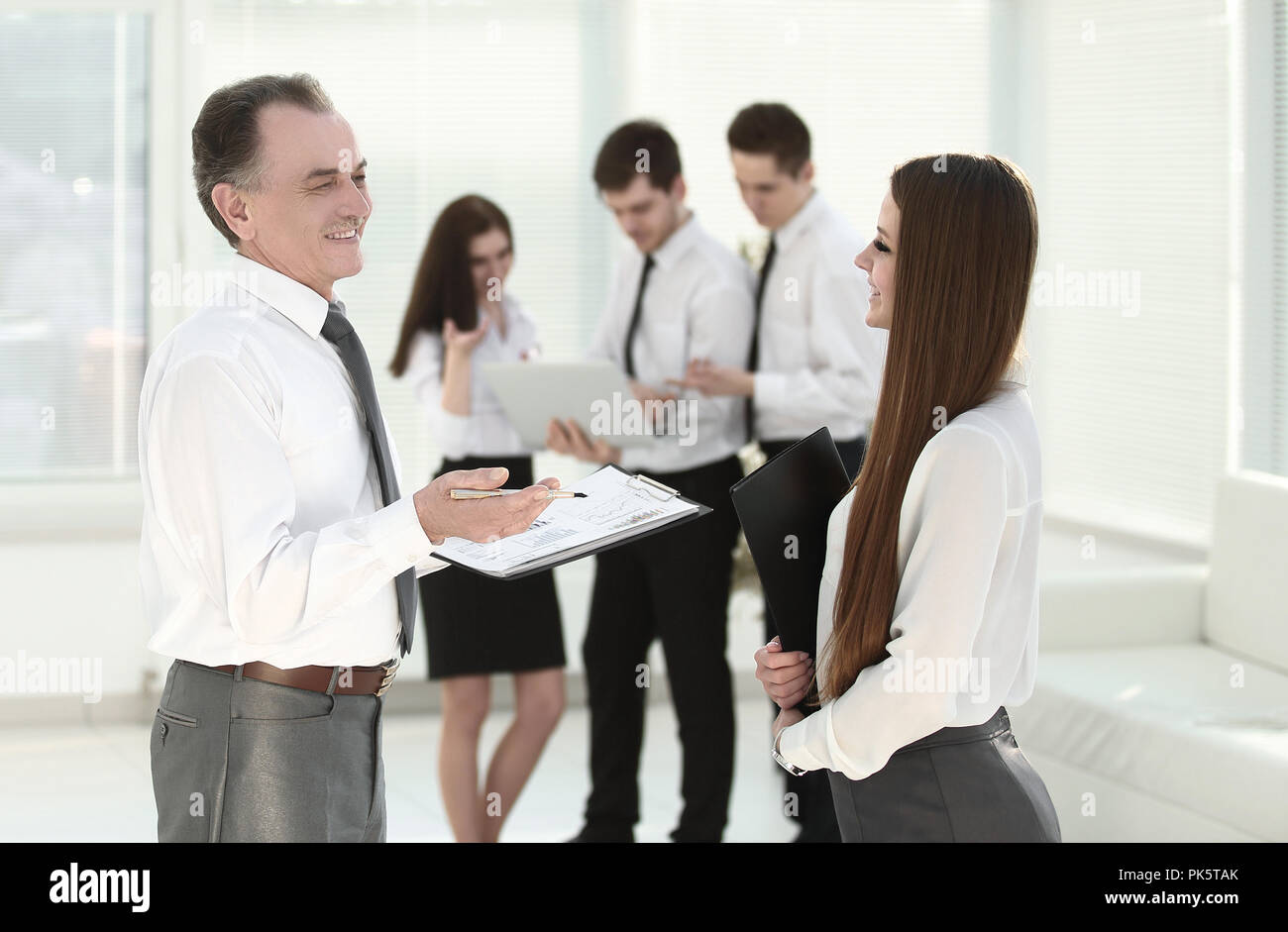 senior businessman discussing a financial report with the employee - Stock Image